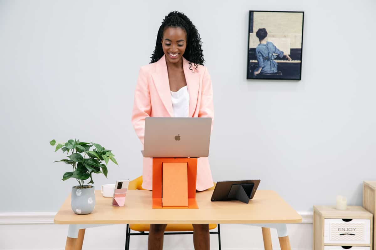 girl at home standing whilst typing on her laptop smiling