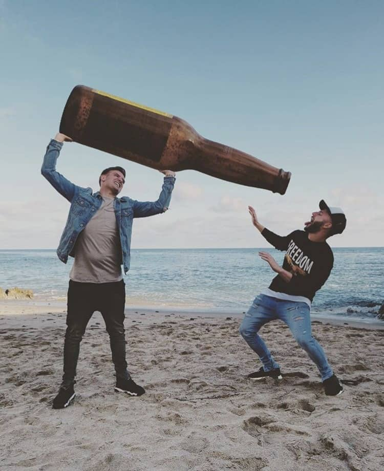 Instagram influencers Woody & Kleiny drink from over sized beer bottle on a beach