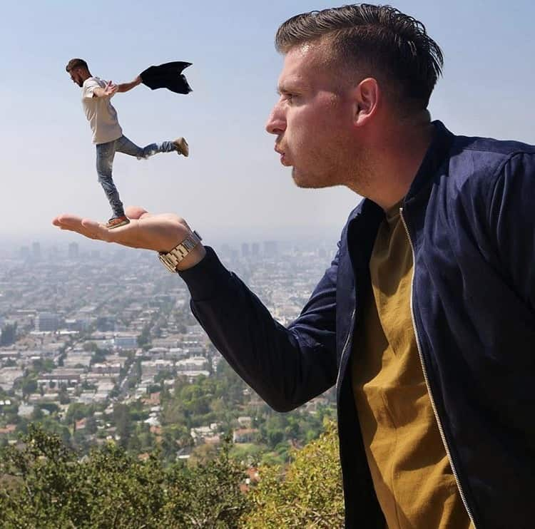 Woody blows an undersized Kleiny from the palm of his hand over a city backdrops